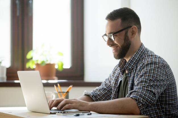 Homem digitando um conteúdo em um notebook